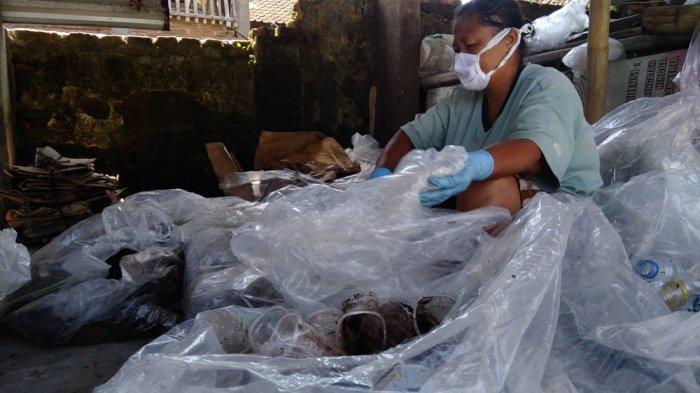 Anggota Bank Sampah Rukun Santoso, Sri Wahyuni memilah sampah di rumah sampah Bank Sampah Rukun Santoso, Senin (19/4/2021). Setelah dipilah, sampah dikategorikan menjadi sampah layak jual, layak kreasi, layak kompos dan layang buang.