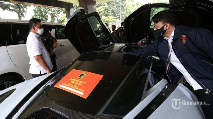Direktur Tindak Pidana Ekonomi Khusus (Dirtipideksus) Bareskrim Polri Brigjen Pol Helmy Santika menunjukkan barang bukti kasus investasi ilegal E-Dinar Coin (EDC) Cash di Bareskrim Polri, Jakarta, Kamis (22/4/2021). Penyidik Bareskrim Polri menetapkan enam orang sebagai tersangka dan menyita 14 kendaraan roda empat, uang tunai dalam mata uang rupiah dan asing, serta barang mewah dalam kasus dugaan investasi ilegal E-Dinar Coin (EDC) Cash. TRIBUNNEWS/IRWAN RISMAWAN