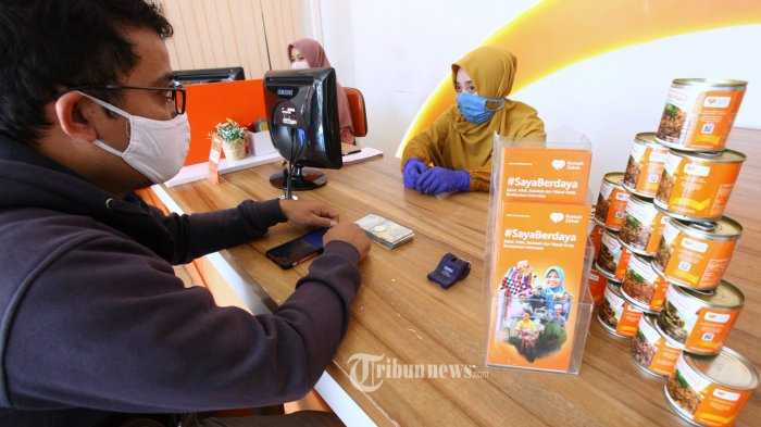 Umat Islam membayar zakat fitrah, infak, dan sedekah di Cabang Kantor Rumah Zakat, Jalan Turangga, Kota Bandung, Selasa (19/5/2020). Zakat, infak, sedekah, dan wakaf (Ziswaf) memegang peranan penting dalam mengatasi dampak dari Covid-19, mulai dari sektor kesehatan, ekonomi, hingga pangan. Untuk sektor kesehatan, dana Ziswaf dapat dimanfaatkan untuk program penyediaan alat perlindungan diri tenaga medis, ventilator, hingga suplemen kesehatan bagi masyarakat yang membutuhkan. (TRIBUN JABAR/GANI KURNIAWAN)