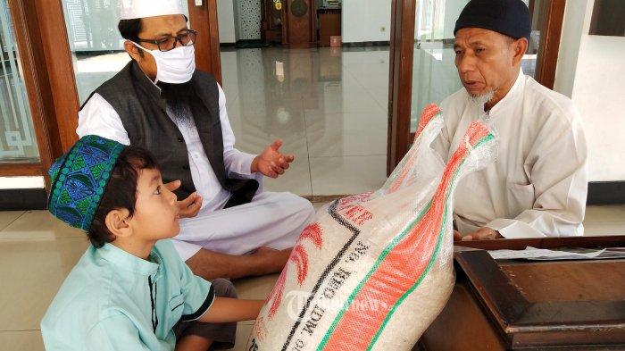 Umat Muslim membayar zakat fitrah, infak, dan sedekah kepada Panitia Zakat DKM Masjid Al-Amanah, Rancamanyar Regency 1, Desa Rancamanyar, Kecamatan Baleendah, Kabupaten Bandung, Sabtu (23/5/2020).