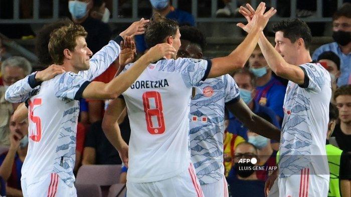 Pemain depan Bayern Munich Polandia Robert Lewandowski (kanan) merayakan golnya dengan rekan satu timnya selama pertandingan sepak bola grup E putaran pertama Liga Champions antara Barcelona dan Bayern Munich di stadion Camp Nou di Barcelona pada 14 September 2021.