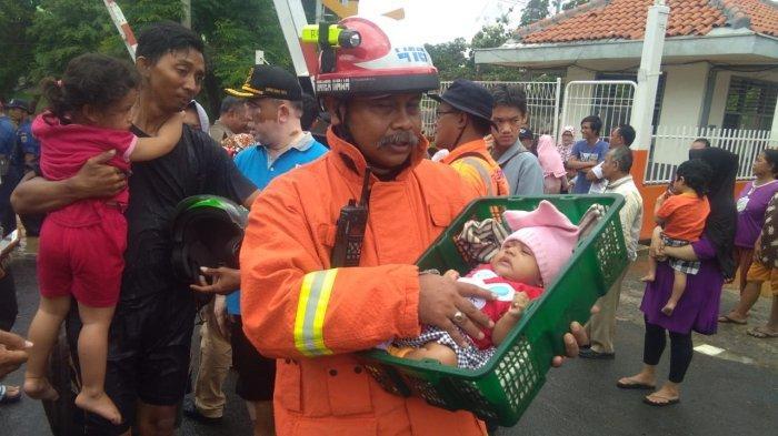 Petugas penyelamat dari Dinas Pemadam Kebakaran Pemprov DKI Jakarta dan warga terharu, upaya evakuasi bayi Sabrina yang 7 jam terjebak banjir di Bukit Duri, Jatinegara, Jakarta Timur, berjalan sukses, Kamis (2/1/2020).