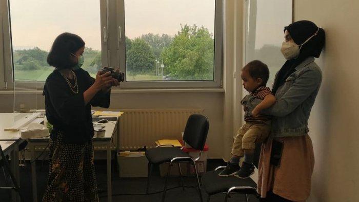 Bayi yang sedang difoto untuk mendapatkan paspor Indonesia