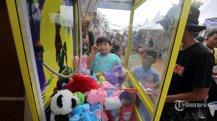 Warga bermain dan berkeliling di arena bazar dan pasar malam yang digelar di Taman Kota Waduk Pluit, Jakarta Barat, Sabtu (28/12/2019). Di arena ini pengunjung dapat menikmati permainan seperti komidi putar, rumah hantu, dan berbagai permainan dengan tiket Rp 10.000 sekali main. Selain itu pengunjung juga dapat berbelanja mulai dari makanan hingga pakaian. Bazar ini akan berakhir pada 2 Januari 2020. Warta Kota/Alex Suban
