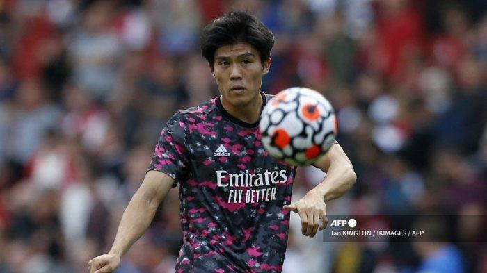 Bek Arsenal asal Jepang Takehiro Tomiyasu melakukan pemanasan jelang pertandingan sepak bola Liga Inggris antara Arsenal dan Tottenham Hotspur di Stadion Emirates di London pada 26 September 2021. Ian KINTGON / IKIMAGES / AFP