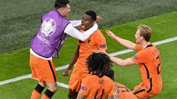 Bek Belanda Denzel Dumfries (tengah) diberi ucapan selamat atas gol ketiga rekan setimnya pada pertandingan sepak bola Grup C UEFA EURO 2020 antara Belanda dan Ukraina di Johan Cruyff Arena di Amsterdam pada 13 Juni 2021. Olaf Kraak / POOL / AFP