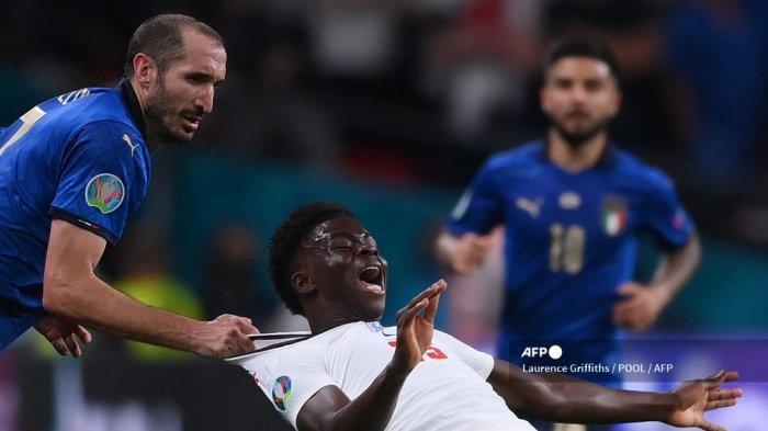 Bek Italia Giorgio Chiellini (kiri) melakukan pelanggaran terhadap gelandang Inggris Bukayo Saka selama pertandingan sepak bola final UEFA EURO 2020 antara Italia dan Inggris di Stadion Wembley di London pada 11 Juli 2021. Laurence Griffiths / POOL / AFP