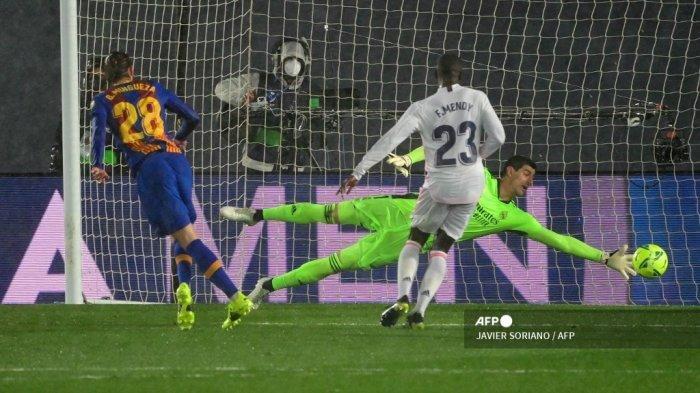 Bek Spanyol Barcelona Oscar Mingueza (kiri) mencetak gol melawan kiper Belgia Real Madrid Thibaut Courtois selama pertandingan sepak bola Liga Spanyol