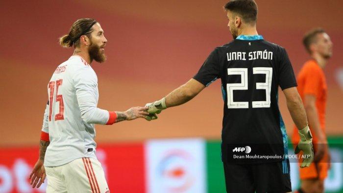Bek Spanyol Sergio Ramos (kiri) berjabat tangan dengan kiper Spanyol Unai Simon di akhir pertandingan persahabatan antara Belanda dan Spanyol di Johan Cruijff ArenA di Amsterdam pada 11 November 2020. Dean Mouhtaropoulos / POOL / AFP