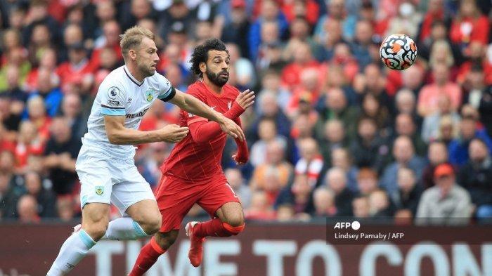 Bek Burnley Inggris Ben Mee (kiri) bersaing dengan gelandang Liverpool Mesir Mohamed Salah selama pertandingan sepak bola Liga Premier Inggris antara Liverpool dan Burnley di Anfield di Liverpool, barat laut Inggris pada 21 Agustus 2021.