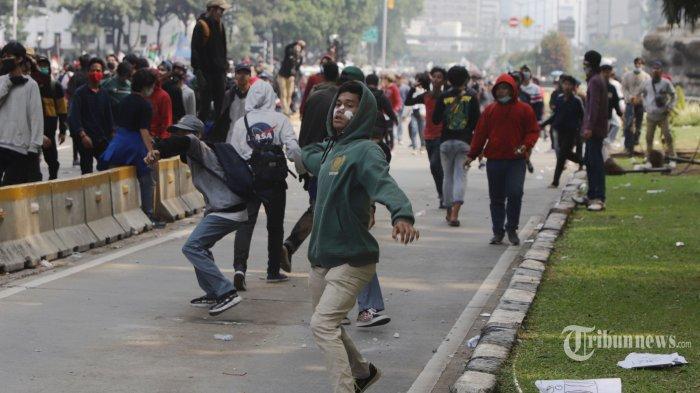 Pengunjukrasa yang berasal dari buruh, mahasiswa, dan pelajar terlibat bentrok dengan polisi saat unjuk rasa di sekitar Patung Kuda Jakarta, Kamis (8/10/2020). Mereka menuntut pemerintah untuk membatalkan UU Cipta Kerja yang dinilai memberatkan pekerja. TRIBUNNEWS/HERUDIN