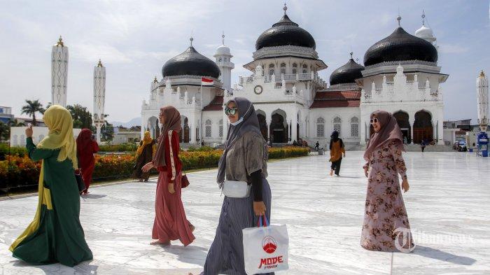 Sejumlah wisatawan berkunjung ke Masjid Raya Baiturrahman, Banda Aceh, Aceh, Sabtu (31/10/2020). Sejumlah objek wisata di Banda Aceh ramai dikunjungi wisatawan domestik dari berbagai kabupaten di Aceh yang memanfaatkan masa cuti bersama dan libur panjang Maulid Nabi Muhammad SAW. Serambi Indonesia/Hendri #TribunNetwork #MataLokalMenjangkauIndonesia