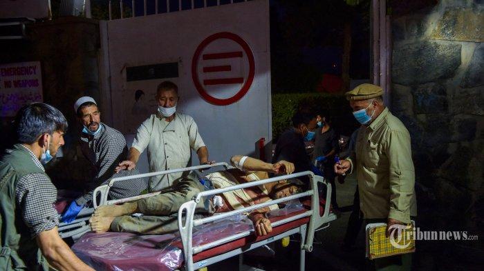 Staf medis dan rumah sakit membawa seorang pria yang terluka dengan tandu untuk perawatan setelah dua ledakan kuat, yang menewaskan ratusan orang, di luar bandara di Kabul, Kamis (26/8/2021). AFP/Wakil KOHSAR