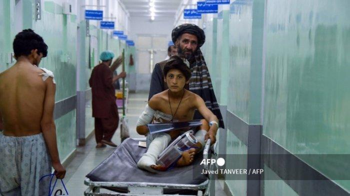 Seorang pria mendorong seorang anak laki-laki yang terluka di atas tandu di sepanjang koridor rumah sakit di Kandahar pada 10 Mei 2021, saat dia menerima perawatan medis setelah terluka oleh bom pinggir jalan yang menghantam sebuah bus semalam yang menewaskan sedikitnya 11 orang.