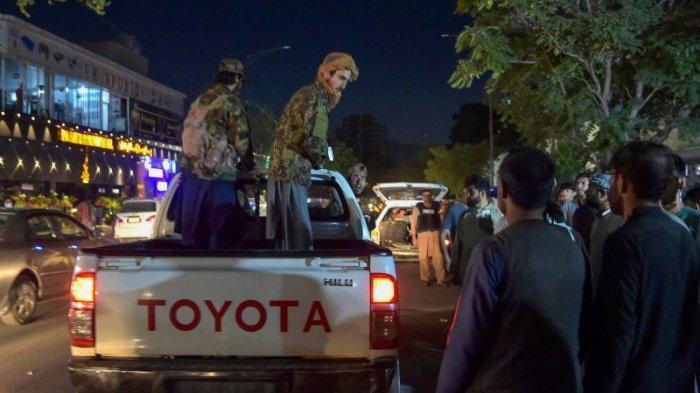 Taliban menunggu di pikap di luar rumah sakit saat sukarelawan membawa korban luka-luka dari ledakan bom di bandara Kabul, Kamis (27/8/2021).