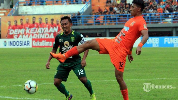 Pemain Borneo FC Lerby Eliandry (kanan)berusaha menjangkau bola dihadang pemain Persebaya Rendi Irwan Saputra pada pertandingan lanjutan Liga1 di Stadion Segiri Samarinda Kalimantan Timur, Jumat 11/5/2018). Dua gol Lerby Imbangi perlawanan Persebaya 2-2. Tribun Kaltim/Nevrianto Hardi Prasetyo.