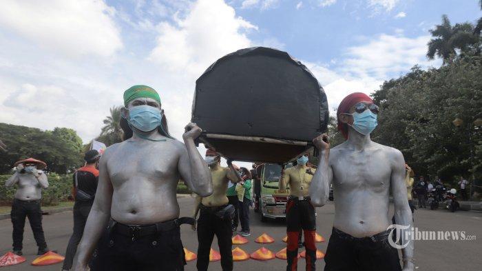 Puluhan buruh melakukan demonstrasi di sekitar Patung Kuda Wijaya, Jakarta, Selasa (29/12/2020). Buruh kembali melakukan demonstrasi untuk menuntut Mahkamah Konstitusi (MK) membatalkan Undang-Undang Undang-Undang Nomor 11 Tahun 2020 tentang Cipta Kerja. Massa KSPI juga mendesak supaya pemerintah menaikkan Upah Minimum Sektoral Kabupaten/Kota (UMSK) tahun 2021. TRIBUNNEWS/HERUDIN