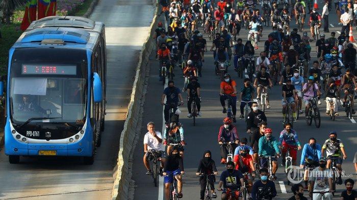 Warga berolahraga saat Hari Bebas Kendaraan Bermotor (HBKB) atau Car Free Day (CFD) di masa Pembatasan Sosial Berskala Besar (PSBB) transisi di kawasan Jalan MH Thamrin, Jakarta Pusat, Minggu (21/6/2020). Pemprov DKI Jakarta kembali menggelar HBKB atau CFD dengan menerapkan protokol kesehatan di sepanjang Jalan Jenderal Sudirman dan MH Thamrin setelah ditiadakan sejak 15 Maret 2020 lalu karena pemberlakuan PSBB untuk mencegah penyebaran virus corona (Covid-19) semakin meluas. Tribunnews/Irwan Rismawan