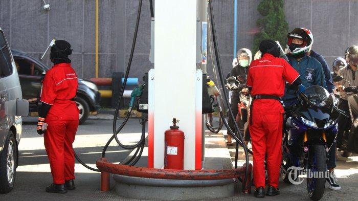 Petugas operator mengenakan masker dan pelindung wahah mengisi bahan bakar minyak (BBM) pada kendaraan bermotor di salah satu SPBU di Kota Bandung, Jumat (12/6/2020). Menghadapi normal baru, Pertamina telah menyiapkan sejumlah protokol kesehatan cegah Covid-19 tambahan di SPBU, untuk konsumen kendaraan roda dua saat melakukan pengisian bahan bakar wajib turun dari motor dan berdiri di samping motor, sehingga tetap dapat menjaga jarak aman dengan memposisikan diri berseberangan dengan operator SPBU. Sedangkan konsumen kendaraan roda empat dapat tetap berada di dalam kendaraan dan apabila diperlukan keluar dari kendaraan wajib menjaga jarak aman minimal 1 meter dari operator. (TRIBUN JABAR/GANI KURNIAWAN)