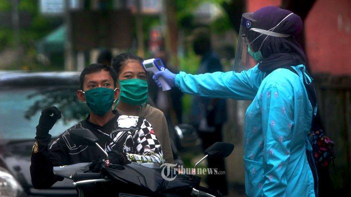 Cek Suhu Tubuh - Petugas melakukan pemeriksaan suhu tubuh pada pengendara roda dua yang berboncengan memasuki Kota Cimahi di jalan HMS Mintareja SH, Baros, Sabtu (02/05/2020). Penerapan Pembatasan Sosial Berskala Besar (PSBB) di Jawa Barat dalam rangka mempercepat penanganan covid-19 akan dimulai 6 Mei mendatang. TRIBUN JABAR/zelphi