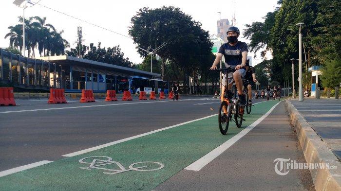 Warga bersepeda melintasi jalur sepeda yang telah dibuat oleh Pemprov DKI Jakarta di Jalan Sudirman, Jakarta Selatan, Minggu (14/6/2020). Pemerintah Provinsi DKI Jakarta hingga sekarang masih meniadakan hari bebas kendaraan bermotor (HBKB) atau car free day (CFD) saat akhir pekan di Jakarta. Namun, Pemprov DKI menyiapkan satu jalur khusus untuk sepeda di sepanjang Jalan Sudirman-MH Thamrin di Jakarta Pusat yang mulai dibuka pada Minggu ini. Warta Kota/Angga Bhagya Nugraha