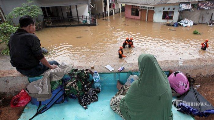 Warga menyaksikan banjir yang merendam permukiman warga di kawasan Cipinang Melayu, Jakarta Timur, Jumat (19/2/2021). Akibat hujan lebat yang mengguyur Ibu Kota Jakarta sejak Jumat dini hari kawasan Cipinang Melayu kembali terendam banjir setinggi 2 meter. Tribunnews/Jeprima