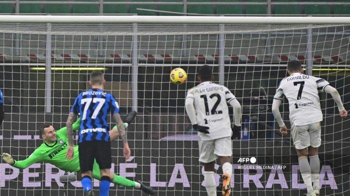 Penyerang Portugal Juventus Cristiano Ronaldo (kanan) mencetak gol penalti melewati kiper Slovenia Inter Milan Samir Handanovic untuk menyamakan kedudukan selama pertandingan sepak bola leg pertama perempat final Piala Italia antara Inter Milan dan Juventus Turin pada 2 Februari 2021 di stadion San Siro di Milan. MIGUEL MEDINA / AFP