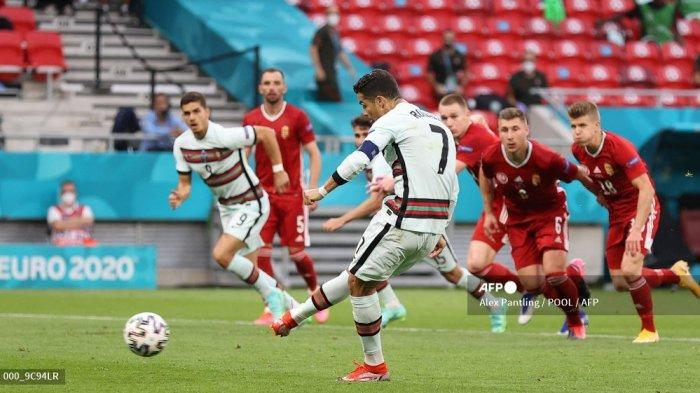 Pemain depan Portugal Cristiano Ronaldo melakukan tendangan penalti dan mencetak gol kedua timnya selama pertandingan sepak bola Grup F UEFA EURO 2020 antara Hongaria dan Portugal di Puskas Arena di Budapest pada 15 Juni 2021.