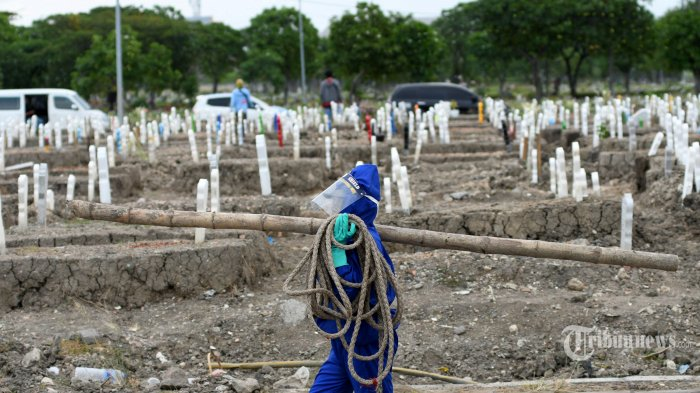 Petugas dengan menggunakan alat pelindung diri (APD) lengkap menyiapkan pemakaman jenazah dengan protokol Covid-19 di TPU Keputih, Kota Surabaya, Jawa Timur, Rabu (15/7/2020). Dari data yang dirilis Gugus Tugas Covid-19 Kota Surabaya per Selasa (14/7/2020), korban meninggal sebanyak 638 orang, pasien positif 7.331 orang, dan pasien sembuh sebanyak 3.700 orang. Sebanyak 1.600 jenazah sudah dimakamkan di TPU Keputih dalam kurun waktu 3 bulan terakhir. Surya/Ahmad Zaimul Haq