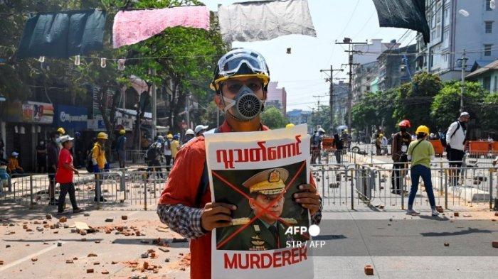 Seorang pengunjuk rasa memegang poster yang menampilkan kepala angkatan bersenjata Myanmar Jenderal Senior Min Aung Hlaing selama demonstrasi menentang kudeta militer di Yangon pada 9 Maret 2021.