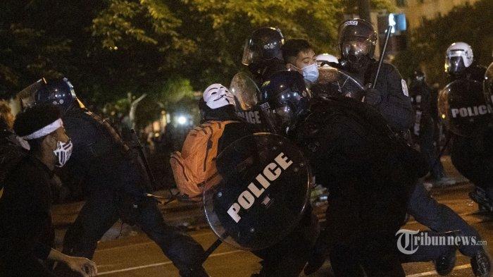 Polisi bentrok dengan demonstran saat warga melakukan aksi unjuk rasa atas kematian George Floyd, di taman dekat Gedung Putih, Washington DC, Amerika Serikat, Minggu (31/5/2020) waktu setempat. Meninggalnya George Floyd, seorang pria keturunan Afrika-Amerika, saat ditangkap oleh polisi di Minneapolis beberapa waktu lalu memicu gelombang aksi unjuk rasa dan kerusuhan di kota-kota besar di hampir seantero Amerika Serikat. AFP/Roberto Schmidt