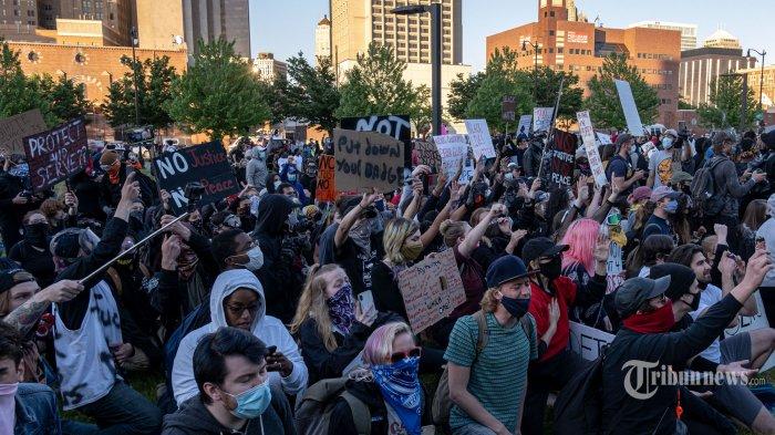 Sejumlah demonstran berlutut dan meneriakkan yel-yel di depan Kantor Polisi Detroit saat melakukan aksi unjuk rasa atas kematian George Floyd, di Detroit, Michigan, Amerika Serikat, Minggu (31/5/2020) waktu setempat. Meninggalnya George Floyd, seorang pria keturunan Afrika-Amerika, saat ditangkap oleh polisi di Minneapolis beberapa waktu lalu memicu gelombang aksi unjuk rasa dan kerusuhan di kota-kota besar di hampir seantero Amerika Serikat. AFP/Seth Herald