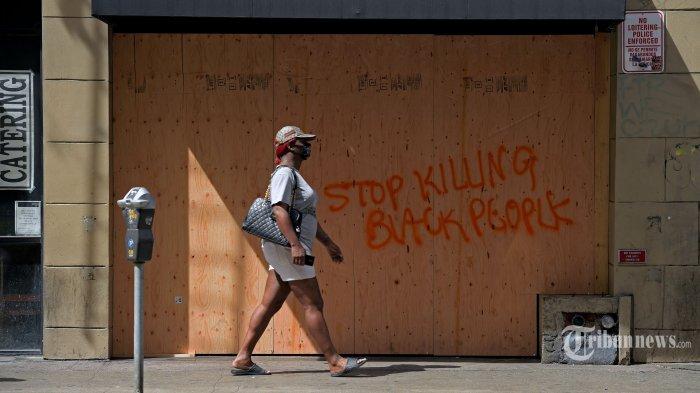 Seorang wanita berjalan melewati sebuah toko yang ditutup dengan papan usai terjadi aksi unjuk rasa atas kematian George Floyd, di Los Angeles, California, Amerika Serikat, Minggu (31/5/2020) waktu setempat. Meninggalnya George Floyd, seorang pria keturunan Afrika-Amerika, saat ditangkap oleh polisi di Minneapolis beberapa waktu lalu memicu gelombang aksi unjuk rasa dan kerusuhan di kota-kota besar di hampir seantero Amerika Serikat. AFP/Agustin Paullier