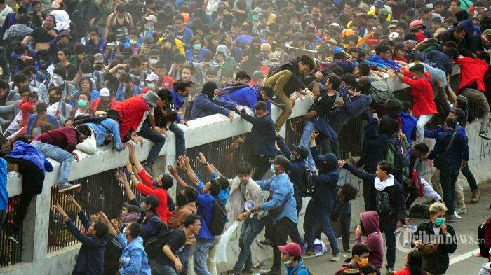 Massa demo meloncati tembok pembatas jalan Tol Dalam Kota karena dipukul mundur oleh polisi dengan dilemparnya gas air mata pada aksi demo di depan Gedung DPR-MPR RI, Jakarta Pusat, Selasa (24/9/2019). Aksi ini dilakukan oleh mahasiswa dari berbagai kampus terkait kontroversi RKUHP dan RUU KPK serta beberapa isu yang sedang bergulir. TRIBUNNEWS.COM/IQBAL FIRDAUS