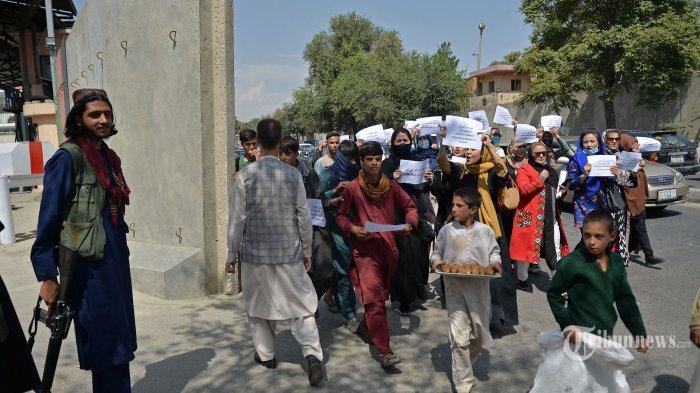 Seorang pejuang Taliban (kiri) berjaga-jaga ketika perempuan Afghanistan mengambil bagian dalam pawai protes untuk hak-hak mereka di bawah pemerintahan Taliban di pusat kota Kabul pada 3 September 2021. AFP/HOSHANG HASHIMI