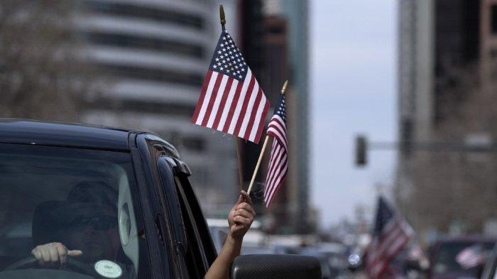 Seorang pengendara mobil melambaikan bendera AS dalam demonstrasi tolak lockdown di Denver, Colorado, Amerika Serikat, Minggu (19/4/2020).
