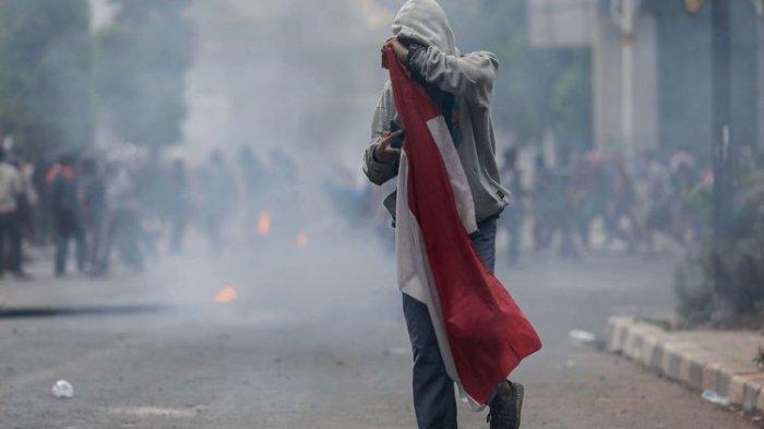 Foto pelajar melakukan Aksi Tolak RUKHP di Belakang Gedung DPR/MPR, Palmerah, Jakarta Barat, Rabu (25/9/2019). Foto ini sempat viral dan pemuda dalam foto itu ditahan polisi.