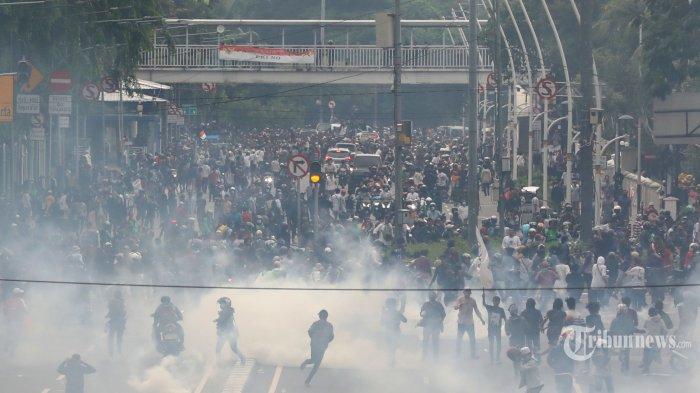 Aparat kepolisian menembakkan gas air mata ke arah massa aksi saat demonstrasi di Gambir, Jakarta, Selasa (13/10/2020). Demonstrasi penolakan UU Cipta Kerja berakhir ricuh. TRIBUNNEWS/IRWAN RISMAWAN
