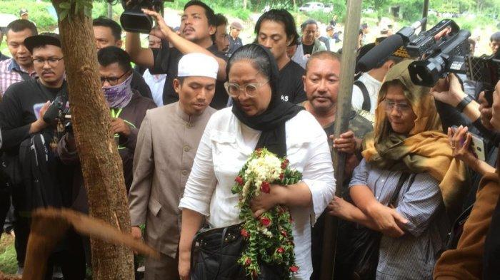 Dewi Irawan saat memegangi karangan bunga di depan makam Ria Irawan, TPU Tanah Kusir, Jakarta Selatan, Senin (6/1/2020).