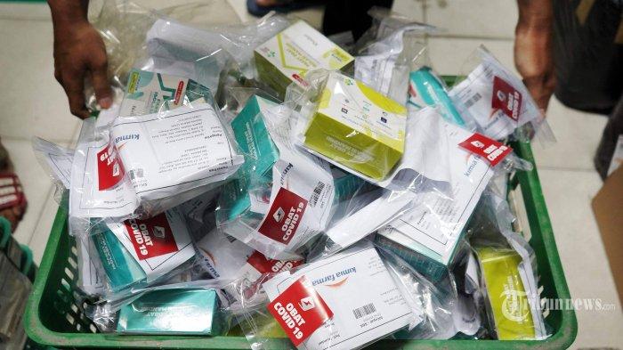 Pekerja memeriksa paket obat dan vitamin untuk pasien Covid-19 yang melakukan isolasi mandiri (isoman), di gerai ekspedisi SiCepat, di Jakarta, Senin (19/7/2021).