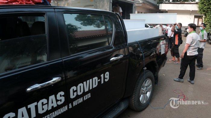 Pekerja memindahkan peti mati ke mobil Satgas Covid-19 di TPU Petamburan, Jakarta Pusat, Selasa (6/7/2021). Dinas Pertamanan dan Hutan Kota DKI Jakarta menyiapkan peti mati untuk jenazah Covid-19 seiring masifnya angka kematian Covid-19 di Indonesia, khususnya di DKI Jakarta. Tribunnews/Irwan Rismawan