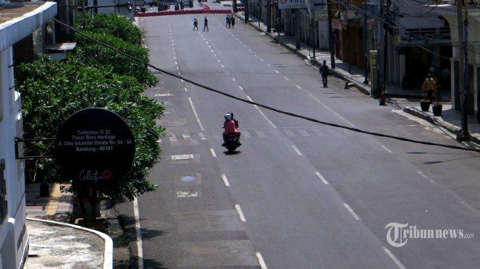 Pengendara sepeda motor melintasi Jalan Oto Iskandar Dinata, Kota Bandung, Jawa Barat, pada saat diberlakukannya Pembatasan Sosial Berskala Besar (PSBB), Kamis (14/5/2020). Kawasan Pasar Baru Kota Bandung ini setiap tahun pada bulan Ramadan menjadi daerah yang selalu dipenuhi pengunjung untuk berbelanja menghadapi Lebaran. Namun, tahun ini dengan adanya pandemi virus corona (Covid-19), kawasan ini diberlakukan sebagai wilayah yang masuk dalam daerah yang tertutup bagi pengunjung sehingga terlihat sepi. Tribun Jabar/Zelphi