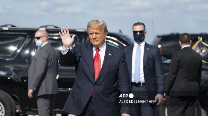 Donald Trump melambai setelah mendarat di Bandara Internasional Palm Beach di West Palm Beach, Florida, pada 20 Januari 2021.