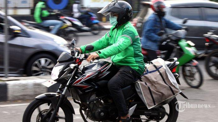 Pengendara ojek online (ojol) mengatarkan barang atau pesanan makanan dan minuman melintas di Jalan Kiaracondong, Kota Bandung, Jawa Barat, Kamis (14/5/2020). Jasa ojol selama penerapan Pembatasan Sosial Berskala Besar (PSBB) di masa pandemi virus corona (Covid-19) hanya melayani pengiriman barang atau mengantar pesanan makanan dan minuman. Tribun Jabar/Gani Kurniawan
