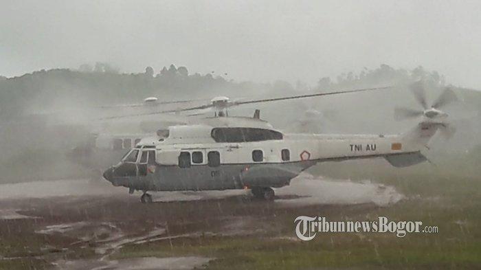 Dua helikopter rombongan yang membawa Sekretariat Presiden dan Staf Presiden sempat menunggu kedatangan helikopter Jokowi saat hujan deras tengah mengguyur kawasan lokasi pendaratan di Lapangan Kantor Kecamatan Sukajaya, Minggu (5/1/2020).