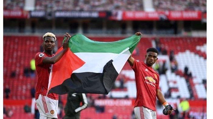 Dua pemain Manchester United, Paul Pogba (kiri) dan Amad Diallo, mengibarkan bendera Palestina di Stadion Old Trafford, Selasa (18/5/2021)