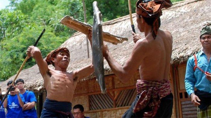 Dua pemain peresean (pepadu) bertarung dalam kesenian tradisional presean di Desa Ende, Lombok, NTB, Minggu (26/11/2017). Peresean merupakan kesenian tradisional suku Sasak yang dulunya diadakan setiap musim kemarau panjang, namun saat ini juga dipertunjukkan untuk wisatawan. (Foto ini di ambil sebelum pandemi Covid-19).