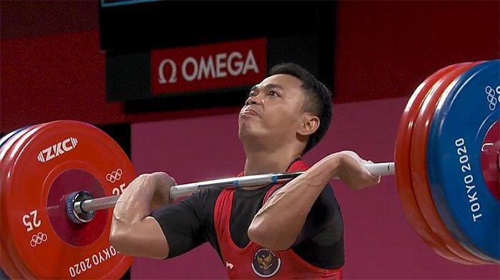 Eko Yuli Irawan sedang berusaha mengangkat besi di kejuaraan angkat besi Olimpiade Tokyo, Minggu (25/7/2021).