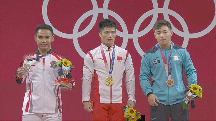 Peraih medali perak pria cabang angkat besi, Eko Yuli Irawan (kiri), Minggu (25/7/2021) berfoto tanpa masker bersama juara pertama dan ketiga (kanan).