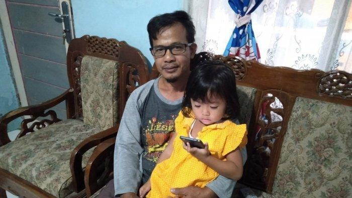 Enjang Imron (48) bersama Adel (4), anak bungsunya, saat ditemui di rumahnya di Jalan Panunggal, Kecamatan Cipedes, Kota Tasikmalaya, Senin (15/2/2021) sore. (TribunJabar.id/Firman Suryaman)